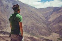 Hombre que se sienta en altas montañas Fotos de archivo