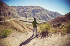 Hombre que se sienta en altas montañas Imagen de archivo