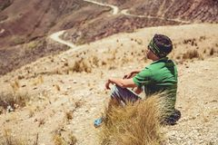 Hombre que se sienta en altas montañas Imagen de archivo libre de regalías