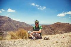 Hombre que se sienta en altas montañas Foto de archivo