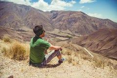 Hombre que se sienta en altas montañas Imágenes de archivo libres de regalías