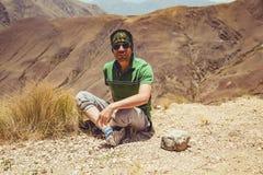 Hombre que se sienta en altas montañas Imagenes de archivo