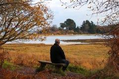 Hombre que se sienta en banco delante de la orilla del mar fotos de archivo