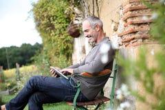 Hombre que se sienta en banco en jardín Imagen de archivo libre de regalías