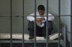 Hombre que se sienta en cama en celda de prisión Imagen de archivo libre de regalías