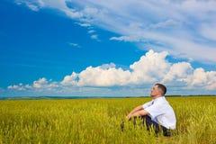 Hombre que se sienta en campo fotografía de archivo