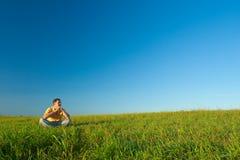 Hombre que se sienta en campo verde foto de archivo