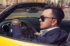 Hombre que se sienta en coche deportivo Foto de archivo libre de regalías