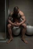 Hombre que se sienta en diarrea del retrete Fotos de archivo