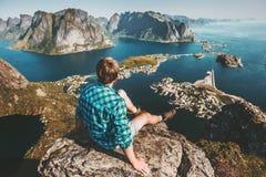 Hombre que se sienta en el acantilado del top de la montaña sobre el mar y rocas foto de archivo