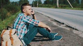 Hombre que se sienta en el camino en campo hitchhiking Ayuda que espera Discurso en el teléfono almacen de metraje de vídeo