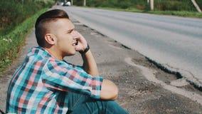 Hombre que se sienta en el camino en campo hitchhiking Para ayuda que espera Coja el teléfono metrajes