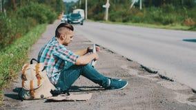 Hombre que se sienta en el camino en campo hitchhiking Para ayuda que espera Mirada del mapa almacen de video