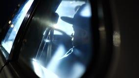 Hombre que se sienta en el coche en la luz en la noche metrajes