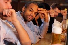 Hombre que se sienta en el contador de la barra Imagen de archivo libre de regalías