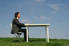 Hombre que se sienta en el escritorio, al aire libre Fotos de archivo libres de regalías