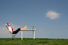 Hombre que se sienta en el escritorio, al aire libre Imagen de archivo libre de regalías