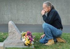 Hombre que se sienta en el gravesite Imagenes de archivo