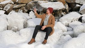 Hombre que se sienta en el hielo y que habla en el teléfono imagen de archivo libre de regalías