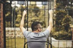 Hombre que se sienta en el oscilación Foto de archivo