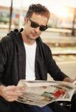Hombre que se sienta en el periódico ferroviario de la lectura de la plataforma Fotos de archivo libres de regalías