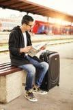 Hombre que se sienta en el periódico ferroviario de la lectura de la plataforma Fotos de archivo