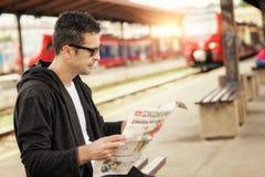 Hombre que se sienta en el periódico ferroviario de la lectura de la plataforma Imagen de archivo libre de regalías