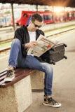 Hombre que se sienta en el periódico ferroviario de la lectura de la plataforma Fotografía de archivo
