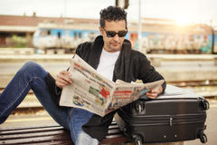 Hombre que se sienta en el periódico ferroviario de la lectura de la plataforma Foto de archivo