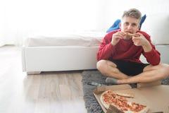 Hombre que se sienta en el piso en la cabecera con una caja de pizza y de un pedazo en sus manos, comiendo los alimentos de prepa fotos de archivo
