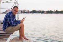 Hombre que se sienta en el puente al lado del mar y que usa la tableta Fotos de archivo