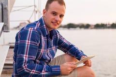 Hombre que se sienta en el puente al lado del mar y que usa la tableta Imagenes de archivo