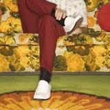 Hombre que se sienta en el sofá. imagen de archivo