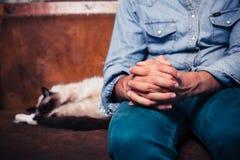 Hombre que se sienta en el sofá con el gato Imagen de archivo