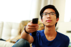 Hombre que se sienta en el sofá que ve la TV en casa Imagenes de archivo