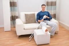 Hombre que se sienta en el sofá con las muletas Imagenes de archivo