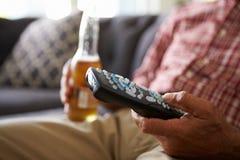Hombre que se sienta en el telecontrol de Sofa Holding TV y la botella de cerveza imagen de archivo libre de regalías