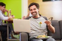 Hombre que se sienta en estudio del diseño de Sofa And Eating Lunch In fotografía de archivo