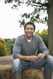 Hombre que se sienta en Haybale al aire libre Fotografía de archivo libre de regalías