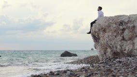 Hombre que se sienta en la alta colina de la roca y que goza sorprendiendo la vista de la playa El hombre de Yung disfruta de la  almacen de metraje de vídeo