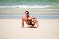Hombre que se sienta en la arena Imagenes de archivo