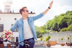 Hombre que se sienta en la bici y la mano que agita fotos de archivo