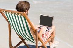 Hombre que se sienta en la butaca en la playa Foto de archivo