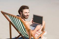 Hombre que se sienta en la butaca en la playa Fotografía de archivo