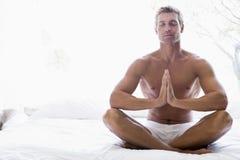 Hombre que se sienta en la cama meditating Fotografía de archivo