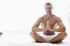Hombre que se sienta en la cama meditating Imagen de archivo libre de regalías