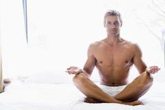 Hombre que se sienta en la cama que hace yoga Fotos de archivo