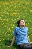 Hombre que se sienta en la hierba Imagen de archivo libre de regalías