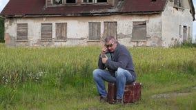 Hombre que se sienta en la maleta y el griterío almacen de video