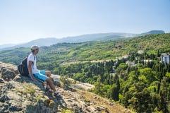 Hombre que se sienta en la montaña Foto de archivo